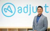 写真:adjust ロゴ前に立つ